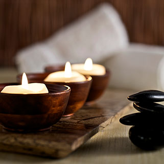 lit candles and massage stones